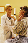Doctor with mature woman patient in her office