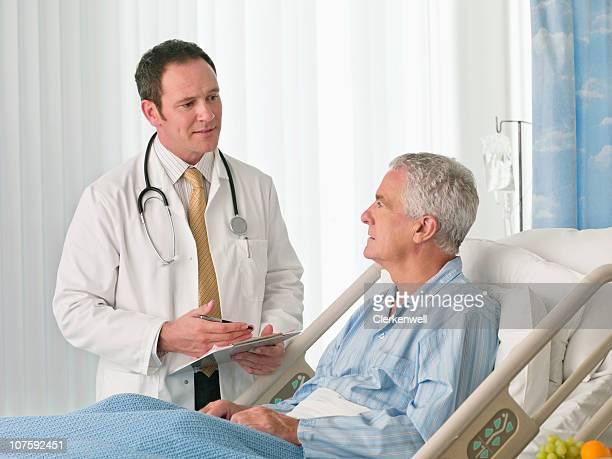 Arzt mit medizinischen Bericht Gespräch mit Patienten im Bett