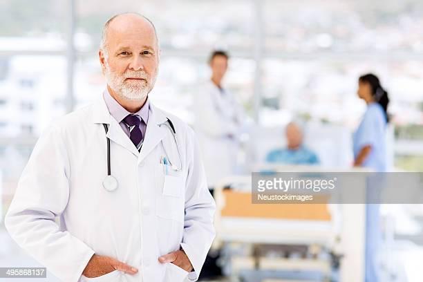 Arzt mit medizinischen Teams und Patienten im Hintergrund