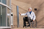 Doctor with muscular dystrophy in wheelchair at hospital entrance pressing knob for accessible door