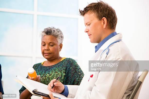 Doutor com paciente a discutir dose de medicamentos sujeitos a receita médica.