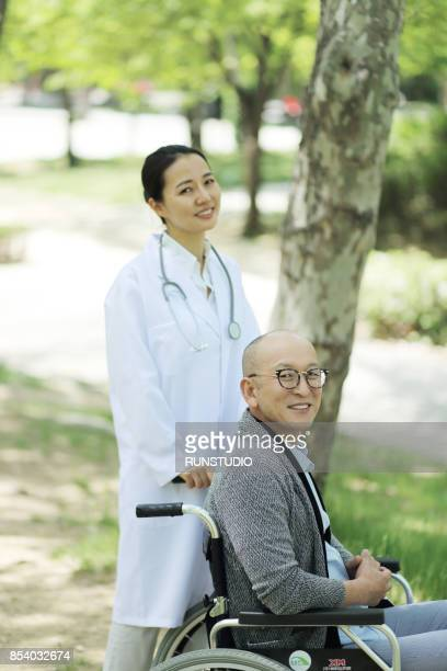 Doctor with senior man in wheelchair