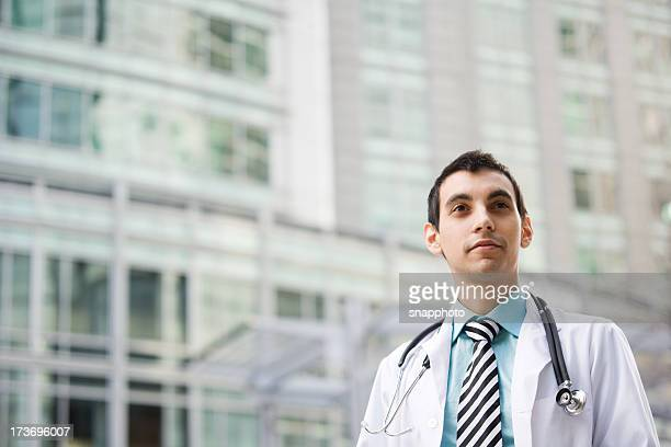 Doctor with stethoscope on neck standing outside