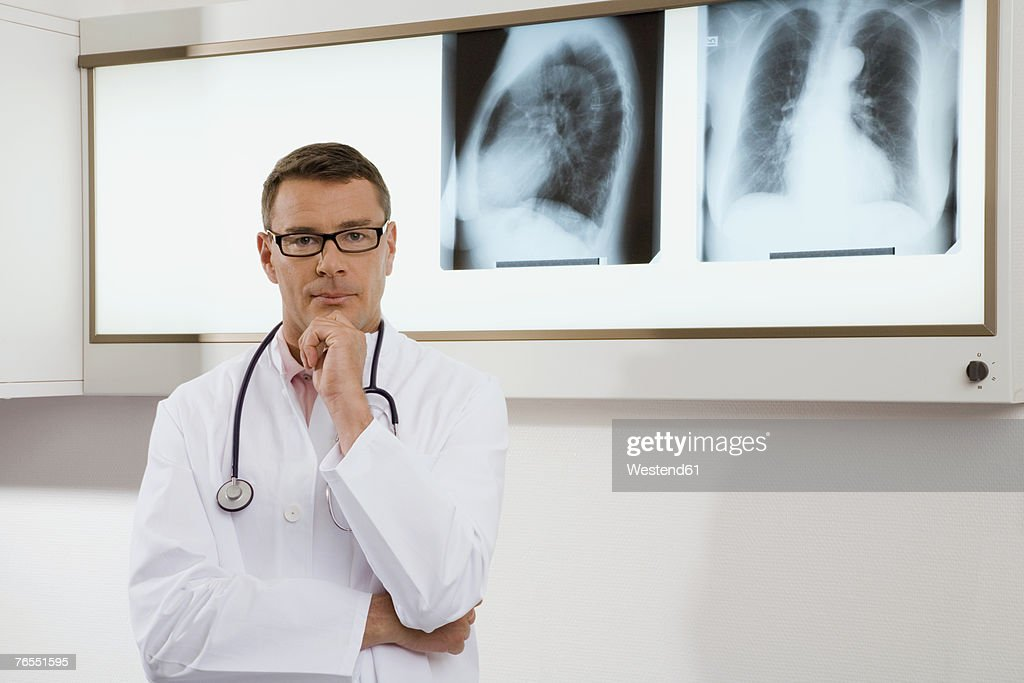 Doctor with stethoscope standing by x-ray image, portrait : Stock Photo