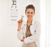 Portrait of doctor woman with eyeglasses in front of snellen chart
