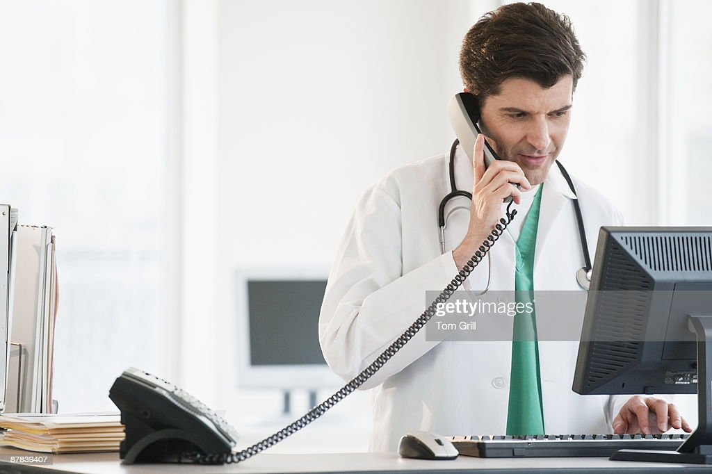 doctor working on computer talking on phone : Stock Photo