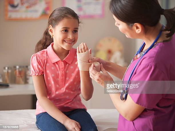 Doctor wrapping ace bandage on child's wrist.