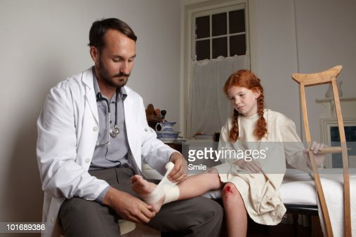 Doctor wrapping little girl's foot with bandage : Stock Photo