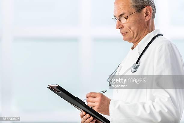 Arzt Schreiben einer medizinischen Diagramm.
