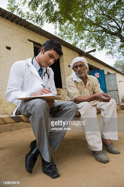 Doctor writing a prescription for a farmer, Hasanpur, Haryana, India