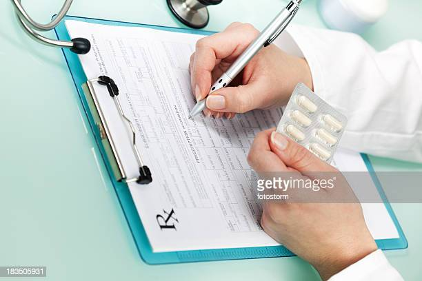Doctor writing a prescription on medical exam, holding pills