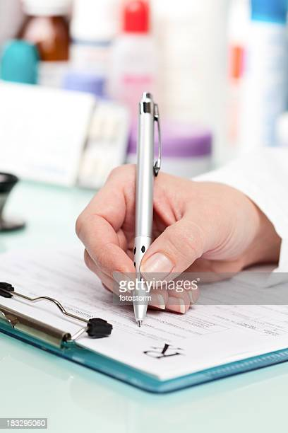 Doctor writing a prescription on medical exam