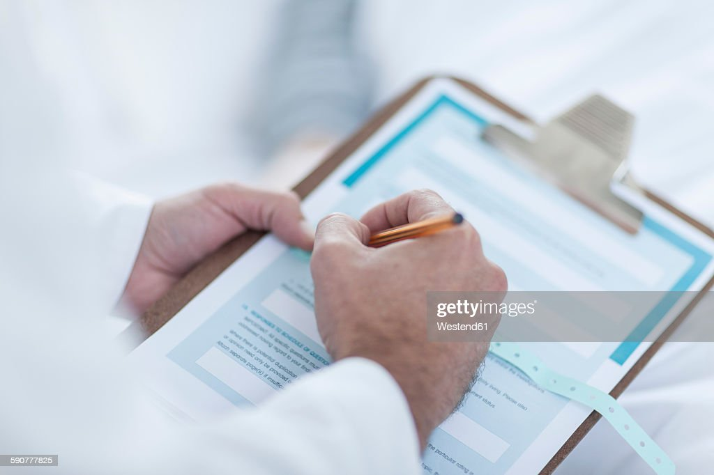 Doctor writing patients name tag in hospital