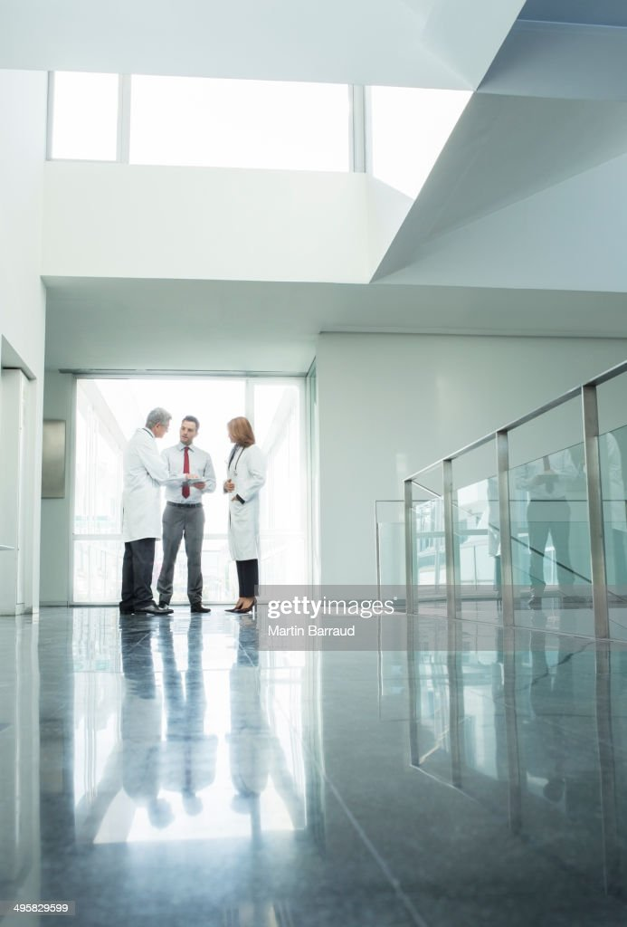 Doctors and administrators talking in hospital corridor