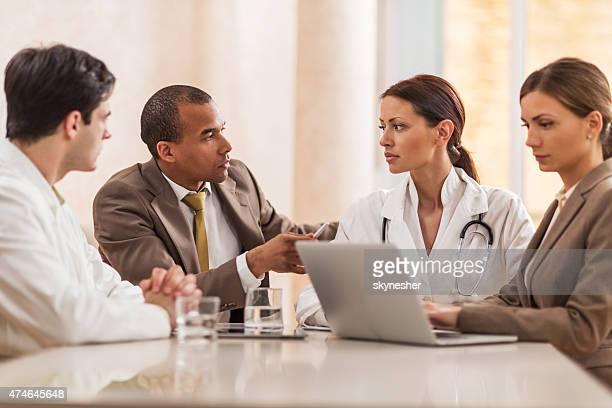 I medici e il personale aziendale collabora in una riunione.