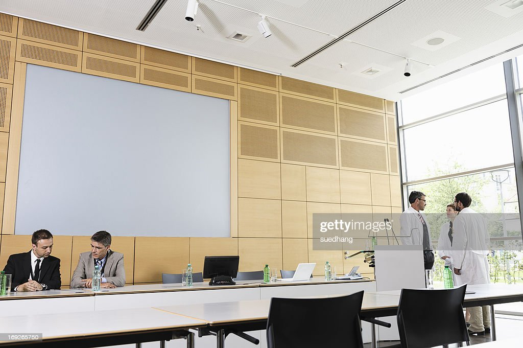 Doctors and businessmen in meeting room : Stock Photo