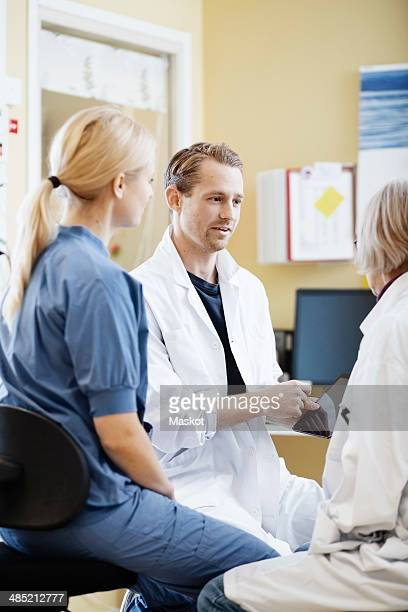 Doctors and nurse discussing over digital tablet in hospital