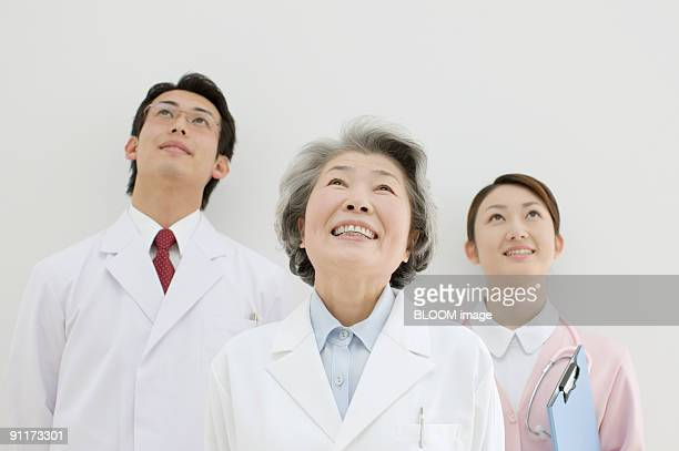 Doctors and nurse looking upward, portrait