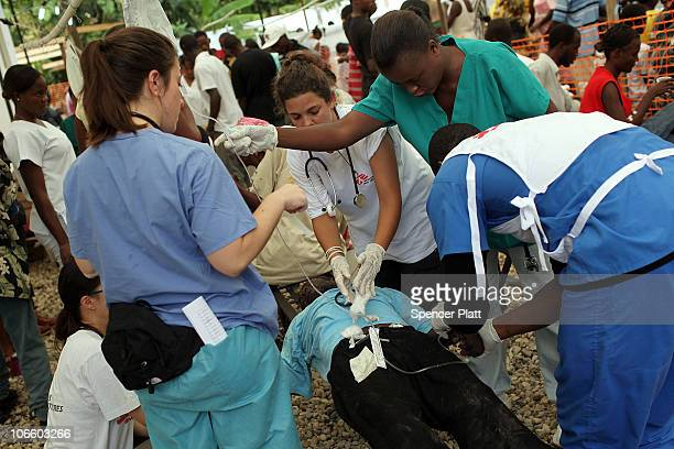 Doctors and nurses aid a man sick with cholera at a hospital run by the Haitian government where Doctors Without Borders is treating cholera patients...