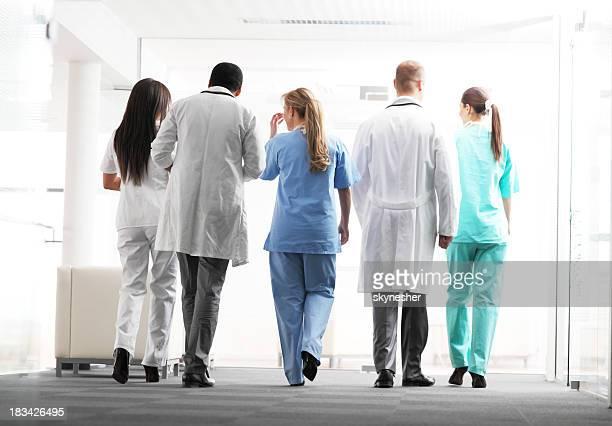 I medici e gli infermieri sono a piedi insieme. Vista da dietro.