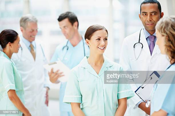 Doctors and nurses discussing in meeting against blur background