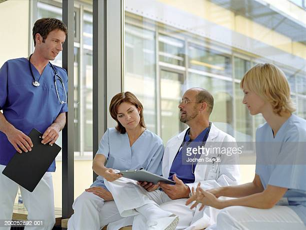 Doctors and nurses talking by window in hospital, smiling
