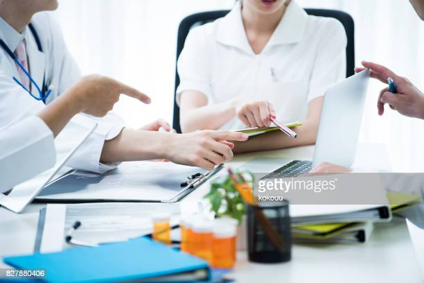 Ärzte sind Verbreitung der Materialien auf der Konferenz-Tisch und reden.