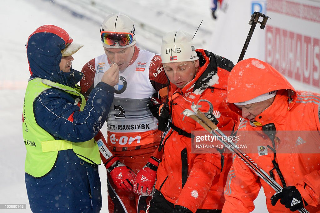 Doctors assist Norway's Emil Hegle Svendsen after he crossed the finish line in third place during the men's 15 km mass start event of the IBU Biathlon Word Cup in the Siberian city of Khanty-Mansiysk, on March 17, 2013. France's Martin Fourcade took the first place ahead of Austria's Dominik Landertinger and Norway's Emil Hegle Svendsen.