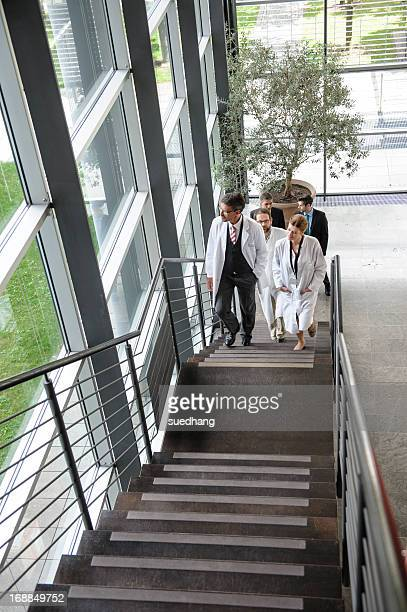 Doctors climbing staircase in office