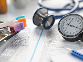 Doctors desk with patients test results, samples, stethoscope and blood pressure gauge