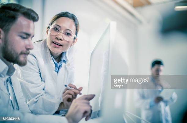 Doctors Discussing and Pointing at X-ray Images on Computer Monitor