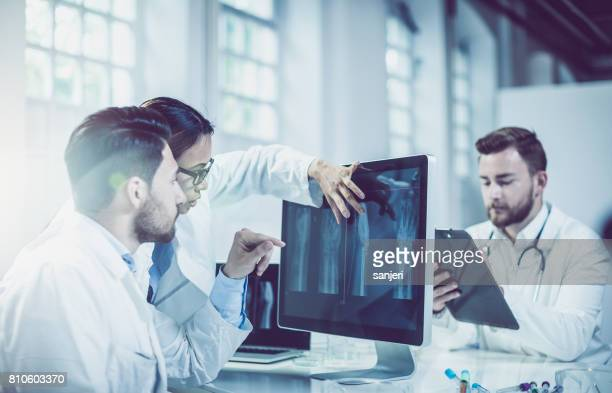Doctors Discussing and Pointing at X-ray Images
