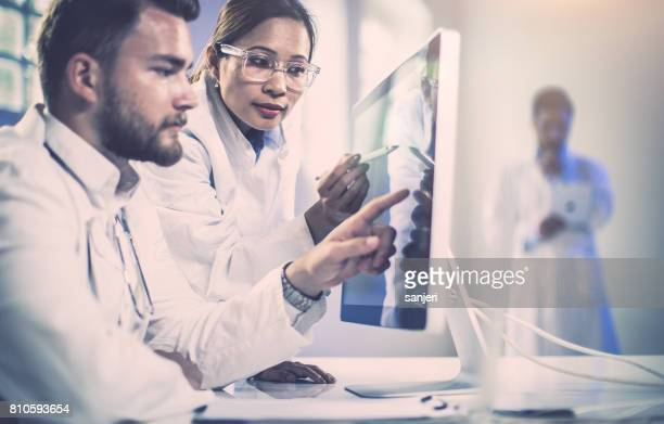 Doctors Discussing and Pointing Computer Monitor