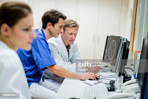 Doctors Discussing CAT Scans on Monitor