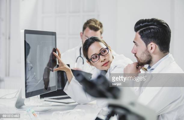 Doctors Discussing X-ray images on Computer Monitor