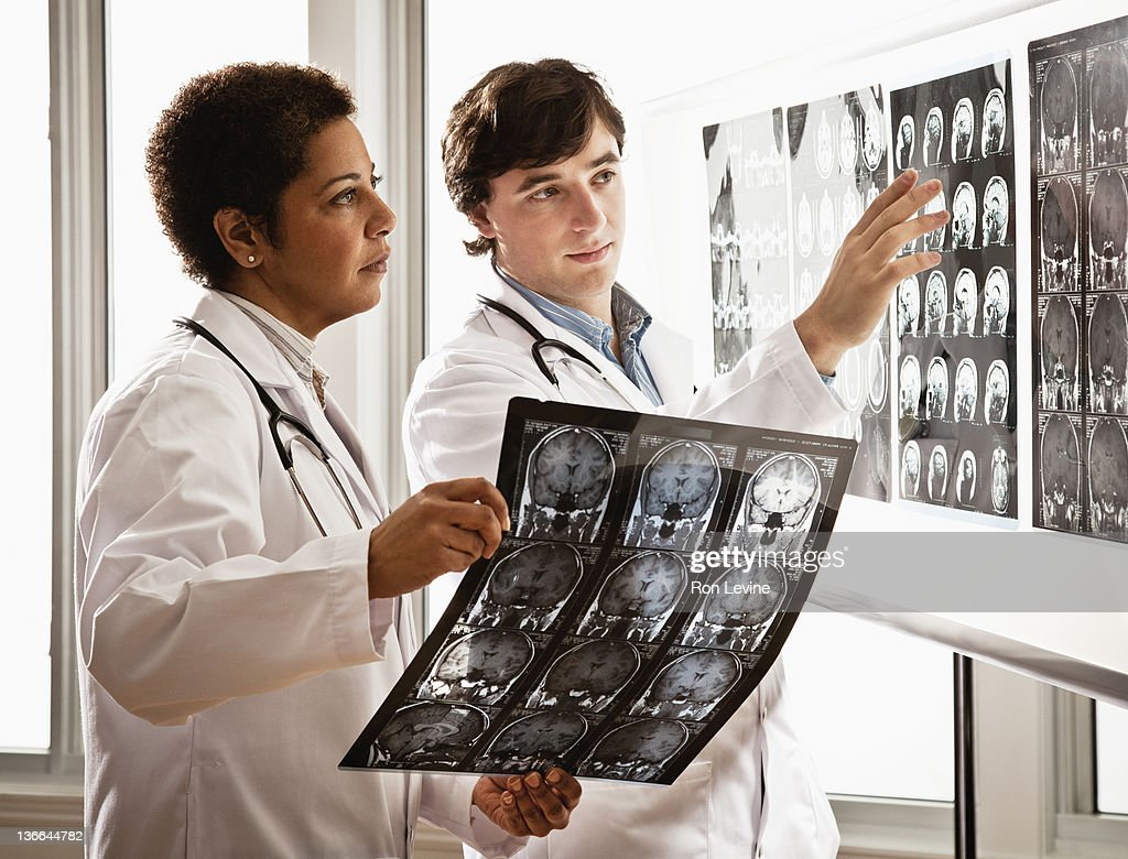 Doctors examining mri scans in radiology clinic : Stock Photo