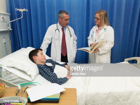 Doctors examining patient in hospital : Stock Photo