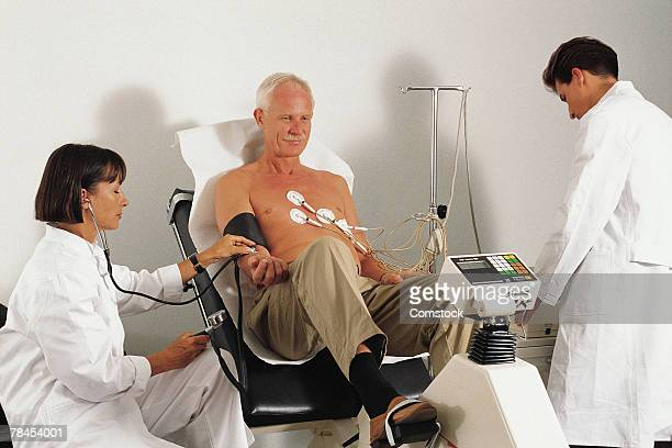 Doctors giving stress test to patient using ergometer