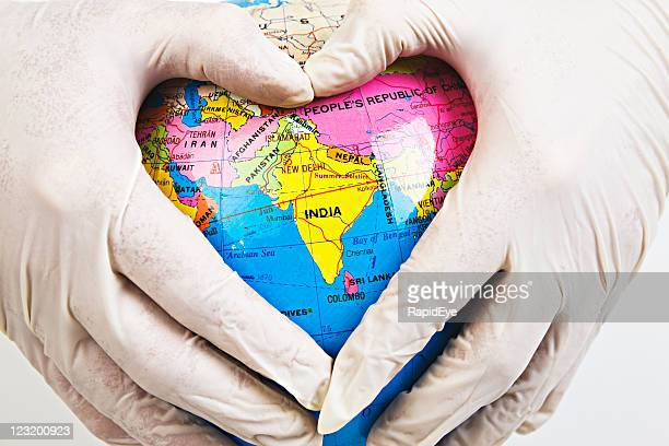 Doctor's gloved hands cradle India in a heart shape
