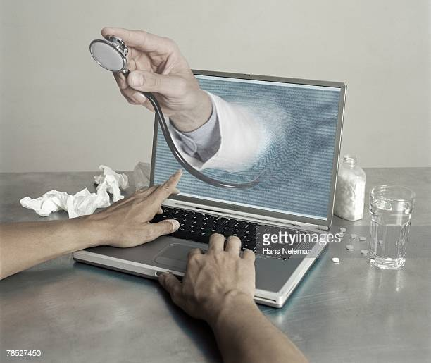A doctors hand coming out of a laptop