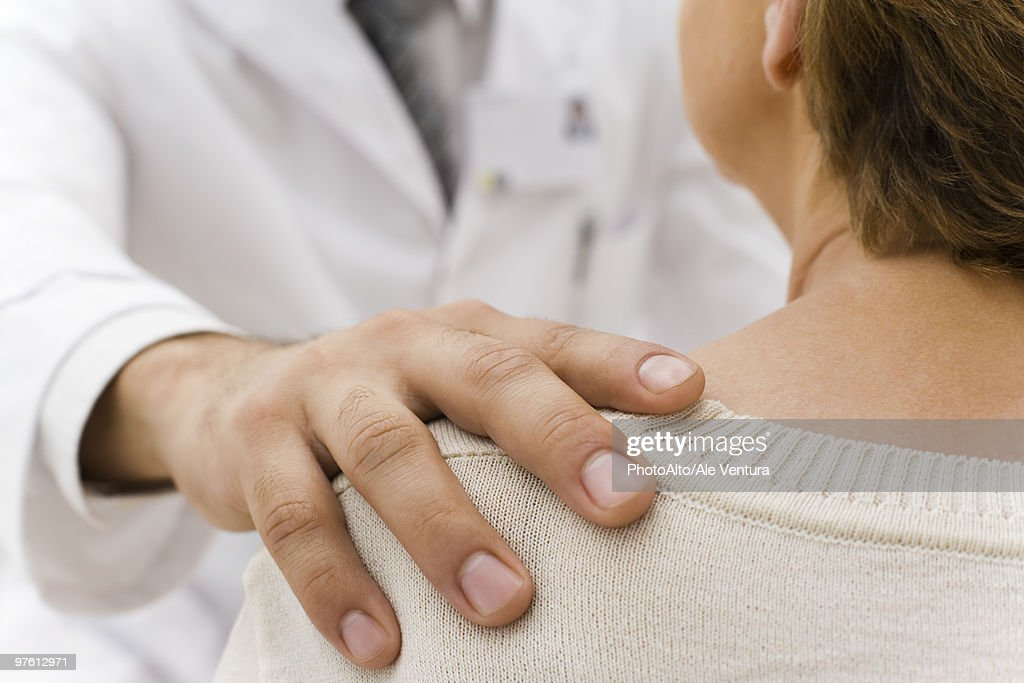 Doctor's hand on patient's shoulder : Stock Photo
