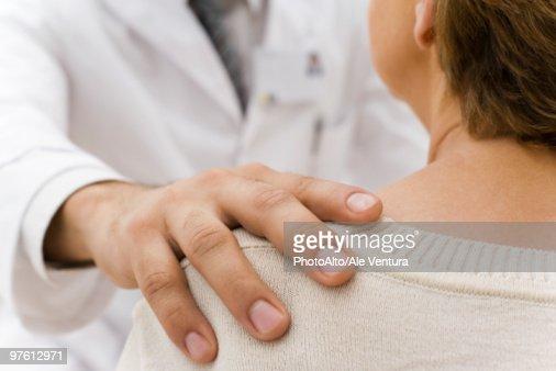 Doctor's hand on patient's shoulder