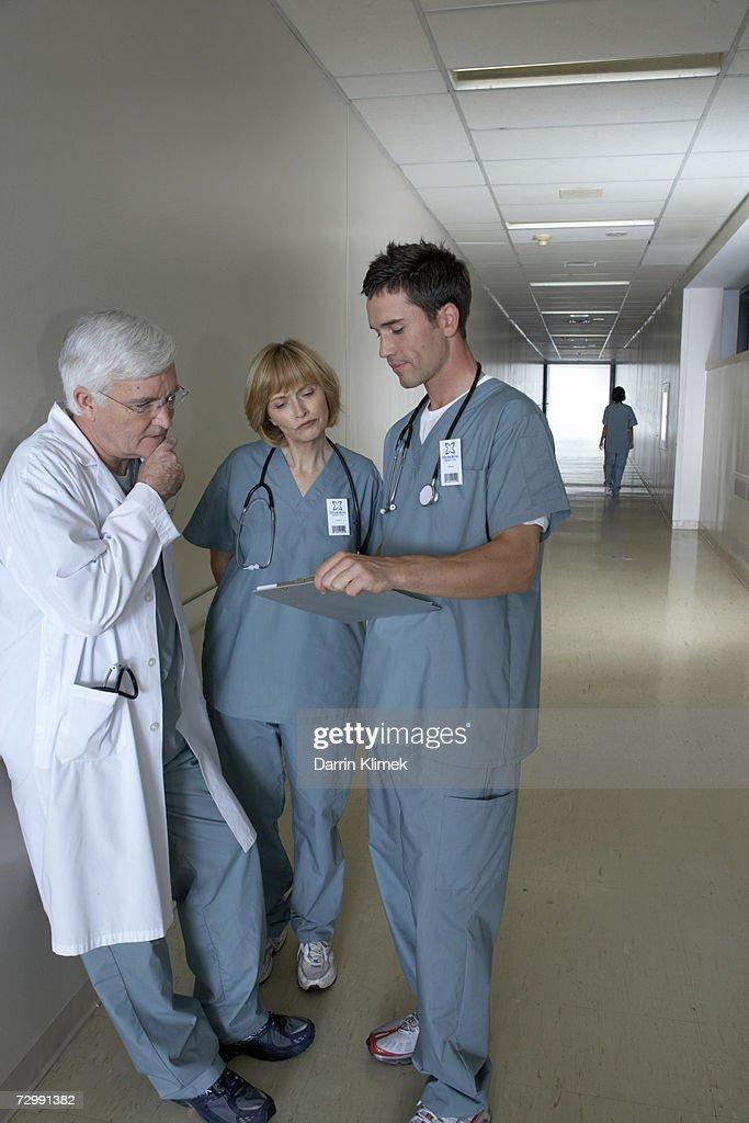 Doctors having discussion in hospital corridor : Stock Photo