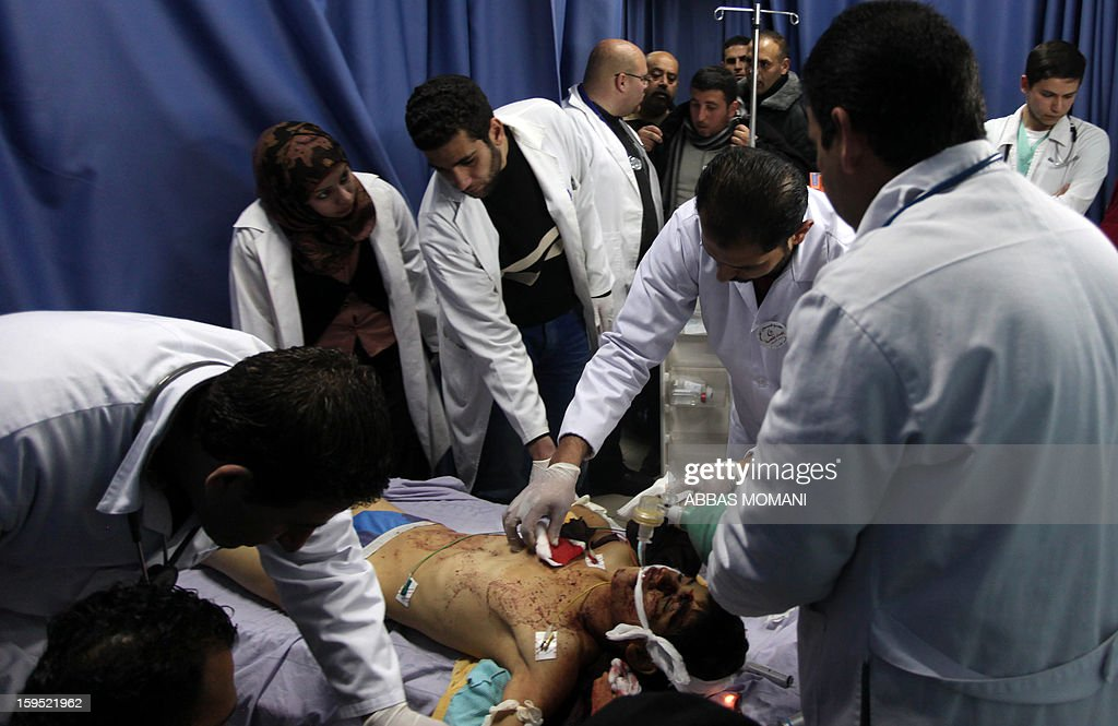 Doctors look at the body of Samir Ahmed Awad, 17, who was shot by Israeli troops not far from Israel's controversial separation barrier, at a morgue near the West Bank city of Ramallah on January 15, 2013. Samir Ahmed Awad died after being hit by a bullet to the chest and another to the leg in an area not far from the village of Ras Karkar, some 10 kilometres (about six miles) northwest of Ramallah, Palestinian medical and security sources told AFP. AFP PHOTO / ABBAS MOMANI