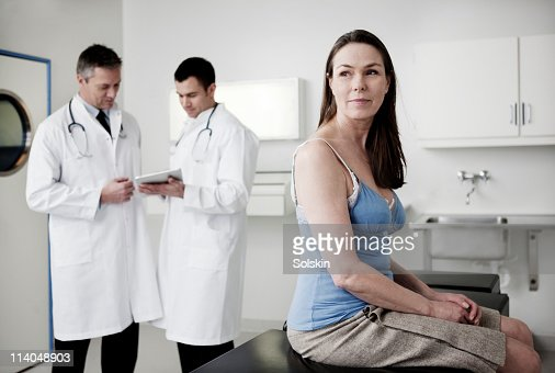 Doctors looking at tablet, patient in foreground : Stock Photo