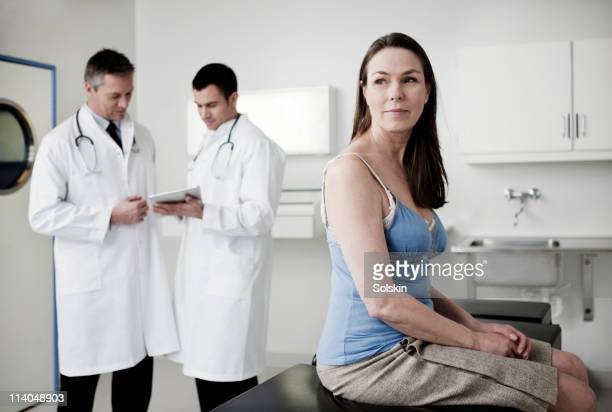 Doctors looking at tablet, patient in foreground