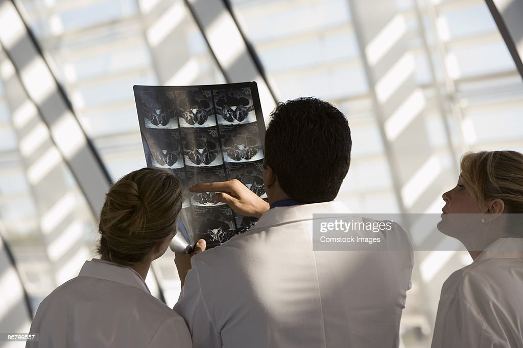 Doctors looking at x-ray : Stock Photo