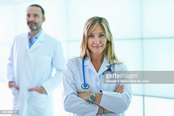 Doctors posing against backlit wall panel
