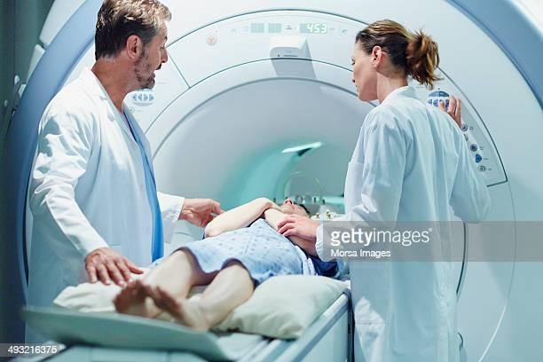 Doctors preparing female patient for MRI scan