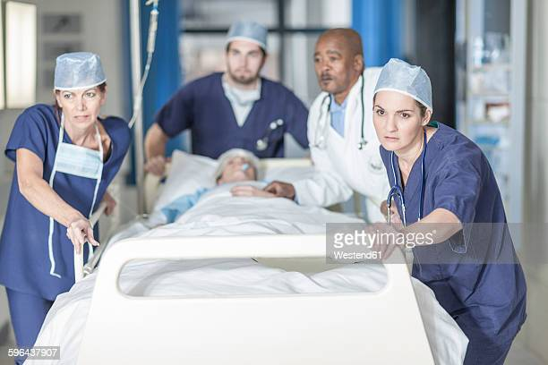 Doctors pushing a bed with patient